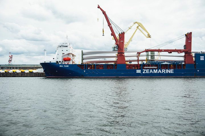 A shipping boat on the water getting shipping containers placed on it