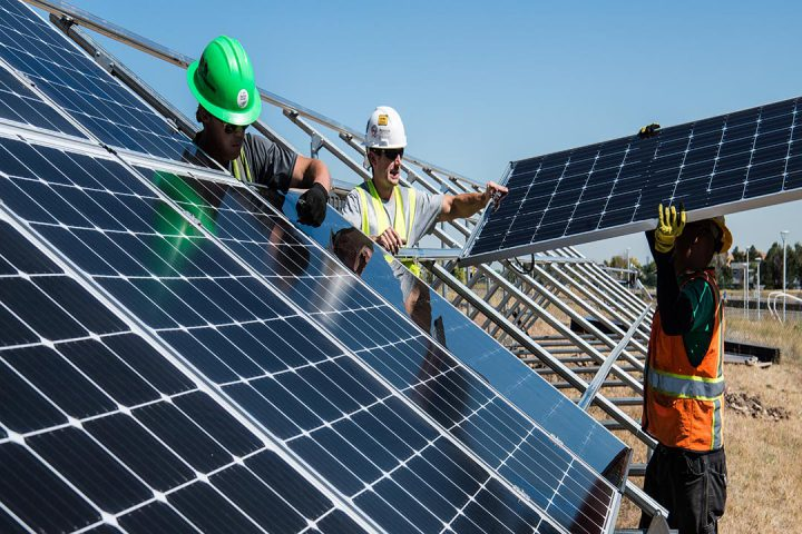 Men putting together a solar panel in a field