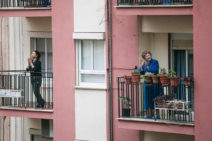 Two neighbours on their apartment building balcony clapping