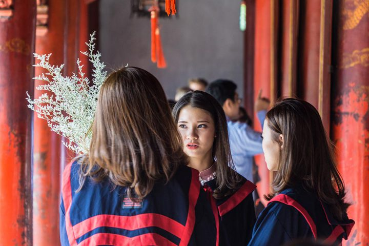 3 women wearing graduation gowns having a conversation